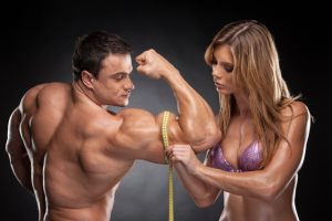 Спортсменка замеряет спортсмену обхват мышц руки