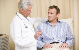 Доктор консультирует пациента о том, почему могут быть болевые или неприятные симптомы в паху