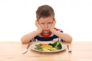 Мальчик сердит и сидит за столом