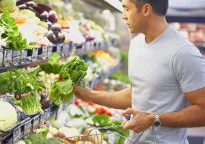 Мужчина выбирает для себя в магазине полезные продукты питания (статья о мужской анатомии)